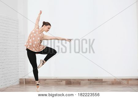 Ballet art concept. Young beautiful ballerina training in dance hall