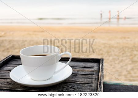 Close up white coffee cup on wood table at sunrise sand beach in the morning Thailand