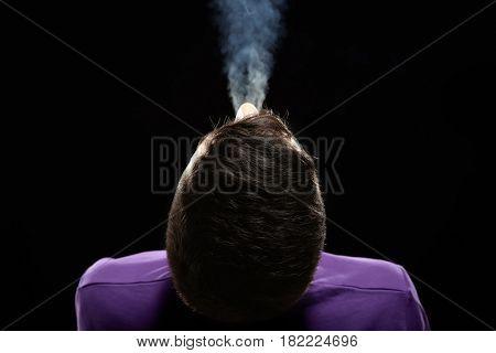 Man exhaling smoke on black background