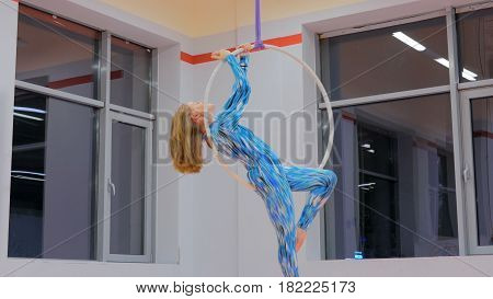 Plastic beautiful girl gymnast on acrobatic circus ring in blue suit. Aerial ring. Acrobatic and sport concept