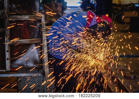 Heavy industrial worker used electric wheel grinding on steel structure in steel factory with sparks.