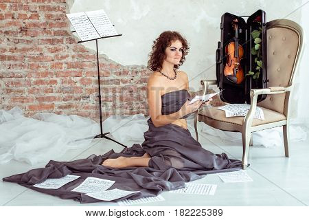 Beautiful woman sitting on the floor near the chair with violin in case and holding notes in hand