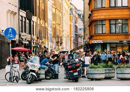 Riga, Latvia - July 2, 2016: Young people meeting and having fun together near parked Motorcycles in the parking lot in Kalku street in sunny summer evening.