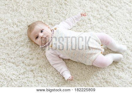 Close-up of a two or three months old baby girl with blue eyes. Newborn child, little adorable peaceful and attentive girl looking surprised at the camera. Family, new life, childhood concept