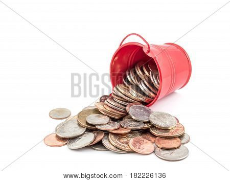 Coins scattered from red pail. Isolated on white.