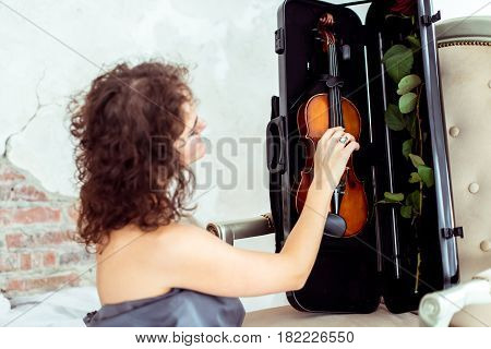 Side view beautiful womansitting near chair and touching violin in the case in studio