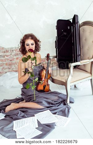 Front view beautiful woman sitting on the floor near chair and holding a violin and smelling red rose flower in studio