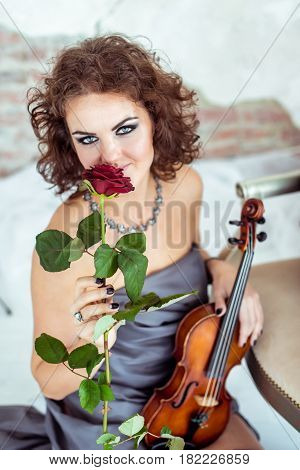 Front view close up beautiful woman sitting on the floor near chair and holding a violin and smelling red rose flower in studio