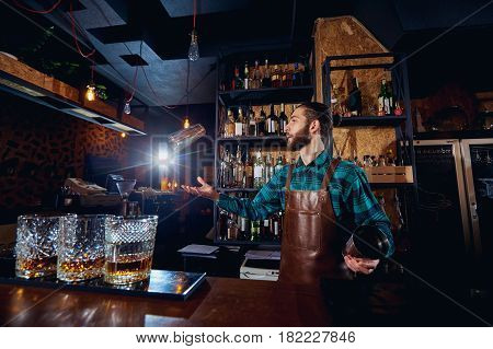 The barman juggler throws up a glass for  cocktail at bar.