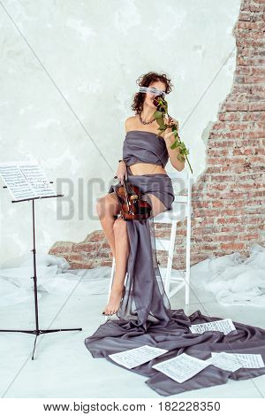 Front view beautiful woman with clear white blindfold holding a violin and smelling red rose flower in studio