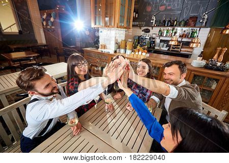 Friends putting their hands  up together in a sign of friendship and teamwork .