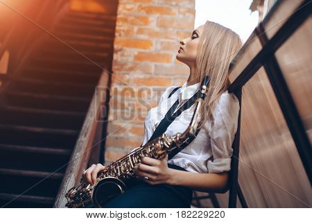 Profile portrait young attractive girl in white shirt with a saxophone - outdoor in old town. Sexy young woman with sax thinking about something.