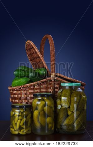 Canned cucumbers in jars and a basket of fresh cucumbers. Canned cucumbers in jars and a basket of fresh cucumbers.Traditional Russian food.