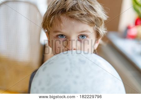 Little blond preschool kid boy with air balloon ball playing indoors at home or nursery. Funny child having fun alone. Happy childhood, kindergarden, school.