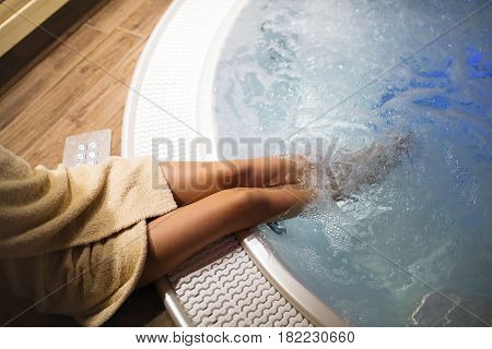 Woman with beautiful legs entering jacuzzi in spa resost
