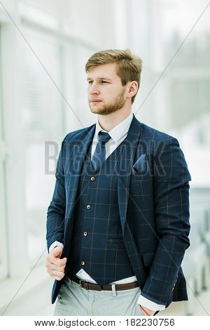 portrait of pensive newcomer businessman in a business suit stands near a window in bright office .the photo has a empty space for your text