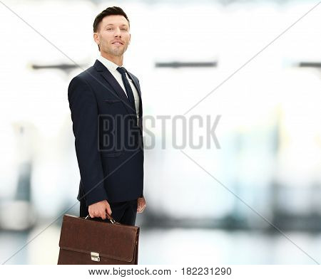 closeup of a corporate lawyer in a black business suit with a briefcase on bright blurred background.the photo has a empty space for your text