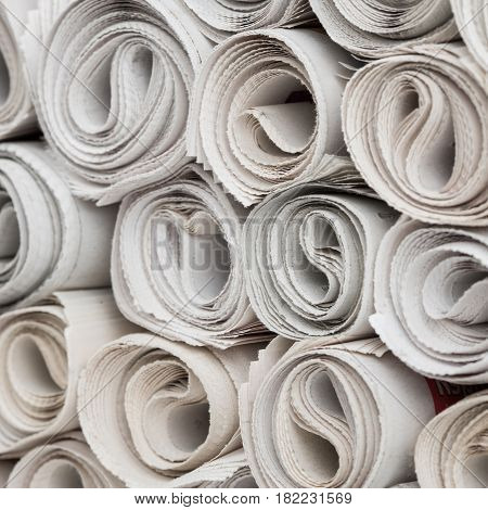 Stack of newspapers rolls, paper texture background.