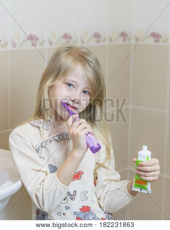 Girl in nightgown with an electric toothbrush in the bathroom. The concept of oral care.
