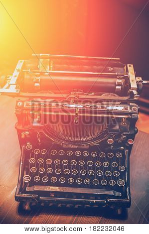 Vintage Typewriter of the early twentieth century, sunlight effect, toned, vertical image with free copy space