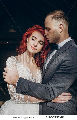 Stylish Bride And Groom Hugging In Light On Background Of Wooden Wall In Barn. Rustic Wedding Concep
