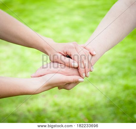 Young hands holding old age hands in front of green background