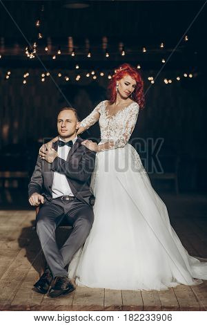 Stylish Groom Sitting And Happy Bride Hugging Him On Background Of Wooden Barn With Retro Lights. Ru