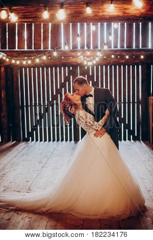 Stylish Groom And Happy Bride Kissing Under Retro Bulbs Lights In Wooden Barn. Rustic Wedding Concep