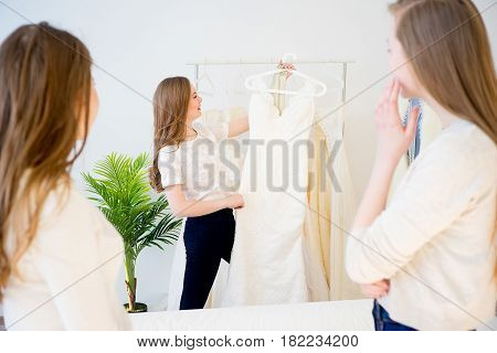 Pretty young woman is choosing a wedding dress in the shop