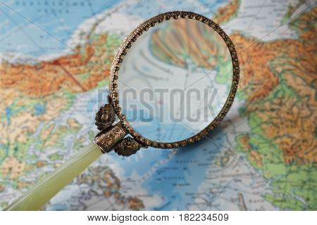 vintage magnifying glass on a blurred map symbol for travel and wanderlust selected focus