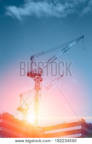 new era of property asset development construction urban rise . crane under-construction building with blue sky sunrise background