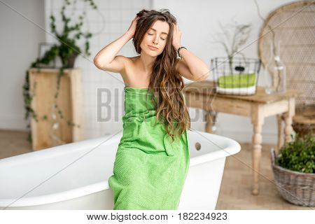 Portrait of a sensitive young woman in green towel sitting in the luxury bathroom