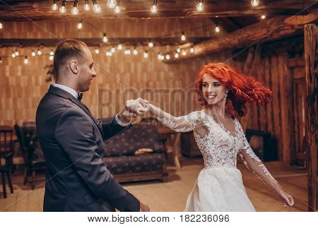 Stylish Groom And Happy Bride Dancing Under Retro Bulbs Lights In Wooden Barn. Rustic Wedding Concep
