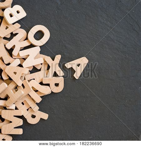 Many wooden letters on black background. Copy space.