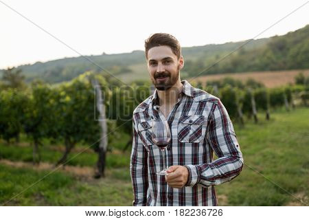 Happy winegrower tasting wine in vineyard in summer