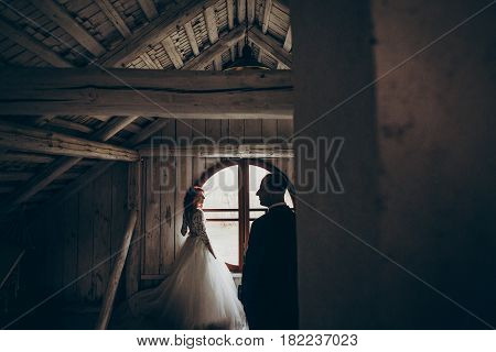 Stylish Groom And Happy Bride Posing Near Round Window In White Wooden Room.  Romantic Moment, Space