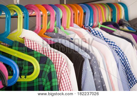 Children clothes on hangers in a room. wardrobe with boy's clothes on hangers. Shopping and consumerism concept .Colorful wardrobe for kids.