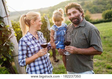 Happy winegrower family in vineyard before harvesting