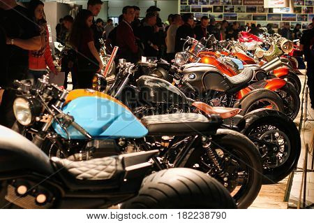 ST. PETERSBURG, RUSSIA - APRIL 16, 2016: - Motorcycles on display at International motorcycle industry salon (IMIS). People visit exhibition center. Selective focus.