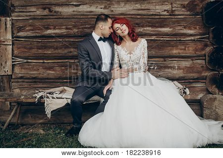 Rustic Wedding Couple Sitting On Bench At Wooden House In Evening. Space For Text. Stylish Groom And