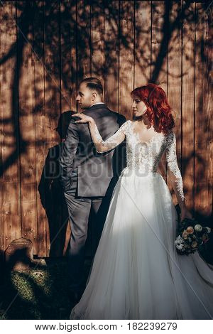 Stylish Bride And Groom Posing In Sunlight On Background Of Wooden Wall In Country. Rustic Wedding C