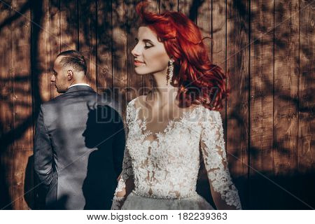 Rustic Wedding Couple Relaxing And Posing In Sunlight At Background Of Wooden Wall In Country. Barn