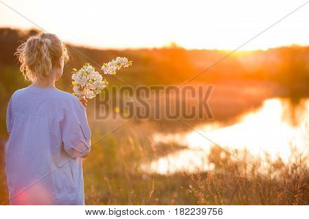 Back view on young woman by the lake on the sunset. Girl with apple trees flowers enjoying summer sunset in the park. Happy woman with bouquet outdoors. Lifestyle and happiness concept