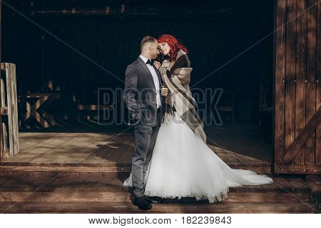Stylish Groom And Happy Bride In Blanket Hugging In Light On Background Of Wooden  Barn. Rustic Wedd