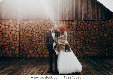 Stylish Groom And Happy Bride In Blanket Hugging In Sun Light On Background Of Wooden Firewood Wall.