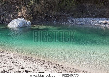 Large stone in the water of a greenish shade.