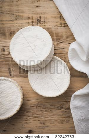 Top view on Camembert cheese on wooden board. Serving French homemade soft cheese. Food concept