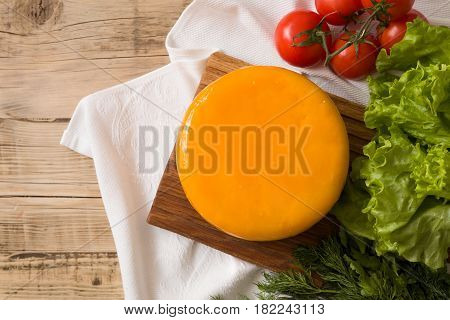 Top view on big cheese head in yellow vacuum package on wooden board served with tomatoes and fresh salad. Serving French homemade cheese. Food concept