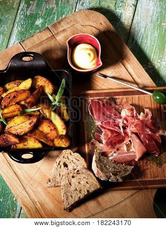 Arrangement of Cured Jamon with Grey Bread and Roasted Potato Wedges with Rosemary in Black Cast-Iron Pan with Cheese Sauce closeup on Wooden Board in Shadow