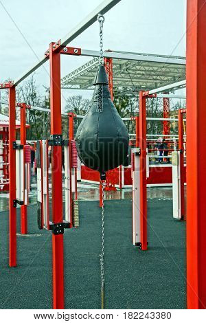 Black leather punching bag on an iron crossbar